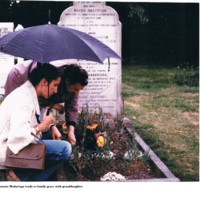 Anastasia Madariaga tends to a family grave with granddaughter.jpg